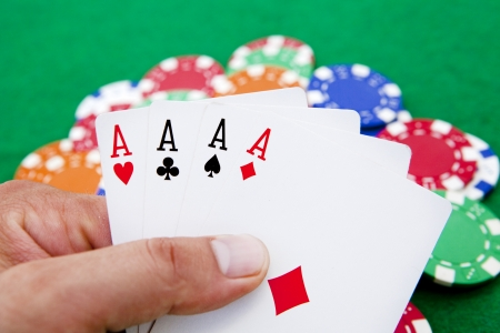 casino table: poker, four aces holded in hand over a casino table full with chips Stock Photo