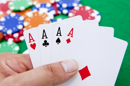 poker, four aces holded in hand over a casino table full with chips photo