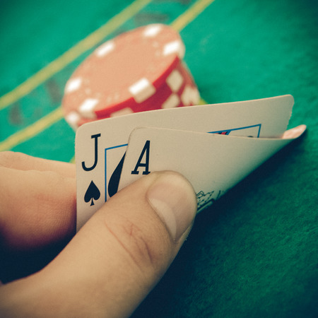 poker chips: Ace of spades and black jack with red poker chips in the background. Stock Photo