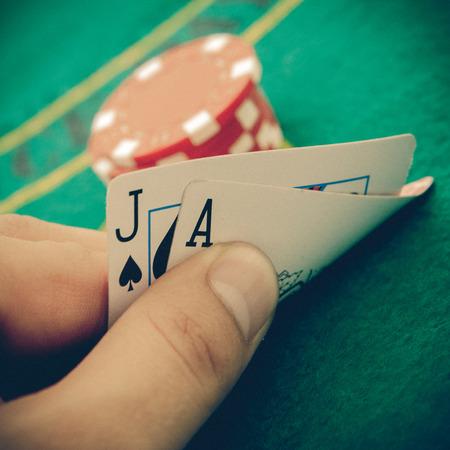 Ace of spades en black jack met rode poker chips op de achtergrond.