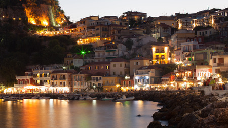 Night in Parga, Greece. A view at fortress, houses and boats near the rocky coast. Redakční
