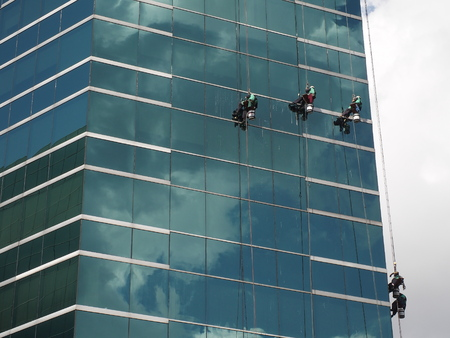 fall protection: men cleaning glass building Editorial