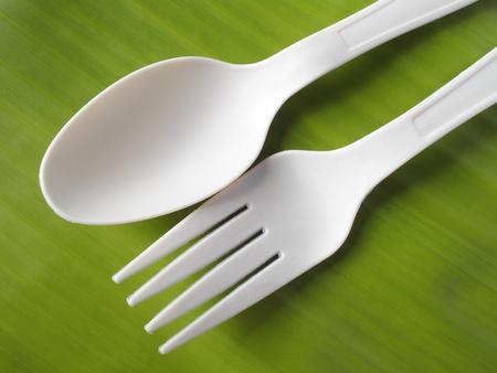 bioplastic spoon and fork on banana leaf background