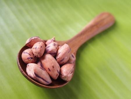 tiger bean in round teakwood spoon on banana leaf background
