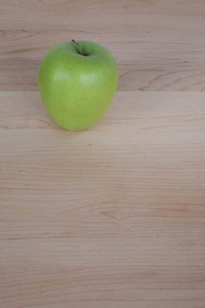 Green Apple on Desk or Cutting Board photo
