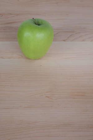 Green Apple on Desk or Cutting Board Stock Photo