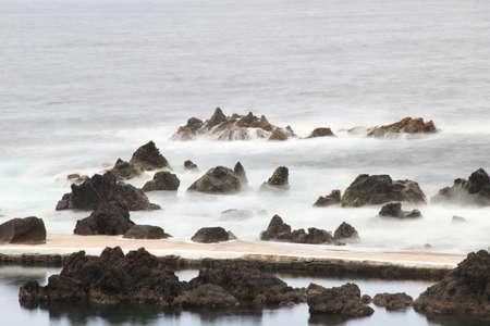 Waves breaking on rocks, silky water, in Porto Moniz Madeira Portugal