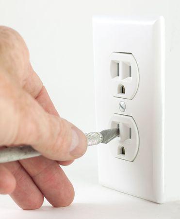 Puede producirse una situación peligrosa cuando poner objetos extraños en una toma de corriente eléctrica, como la electrocución  Foto de archivo - 7675099