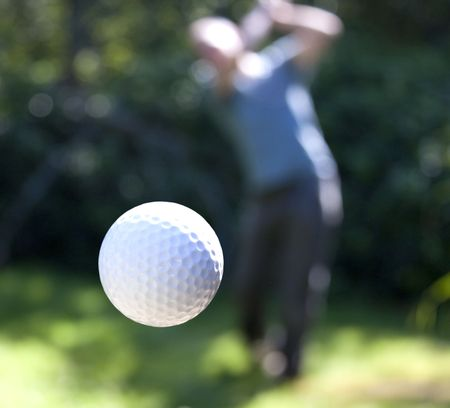 golf green: A golf ball just coming off the tee from a golfer in swing.