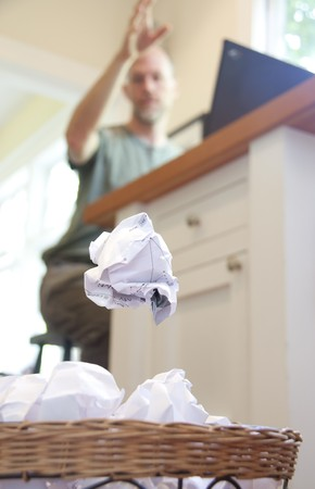 wastebasket: A frustrated man throwing a crumpled piece of paper into an overflowing wastebasket