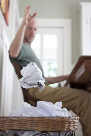 A frustrated man in his home office, throwing away a crumpled piece of paper. Stok Fotoğraf