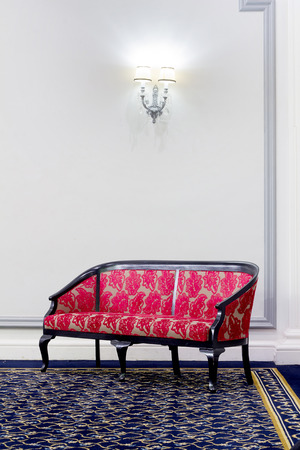 red sofa: red fabric sofa in front of white wall with wall lamp