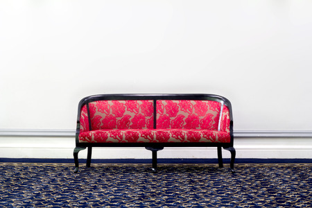 red fabric sofa in front of white wall