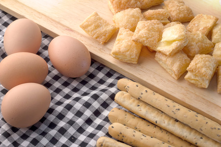 grissini: Fresh baked homemade grissini bread sticks and  crispy pie with egg and wood spoon on vintage fabric background