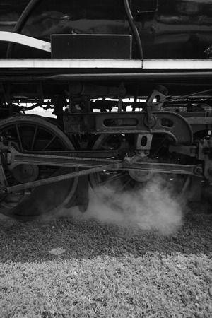 land use: iron wheels of stream engine train on railways track perspective to golden light forward use for old and classic period land transport and retro black and white image