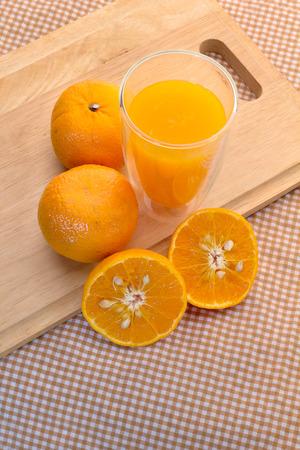 naranja: Naranjas corte establecido y vaso de jugo de naranja sobre base de madera