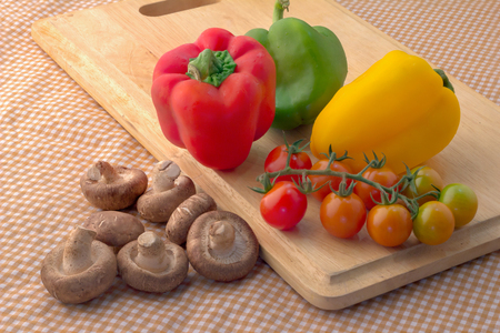 sweet peppers: fresh tomato and mushroom with sweet peppers on wooden plate with brown fabric background Stock Photo