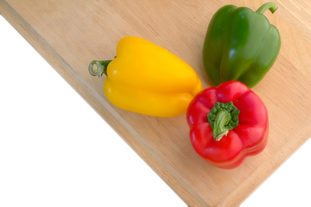 sweet peppers: Three colorful sweet peppers on a wooden background Stock Photo