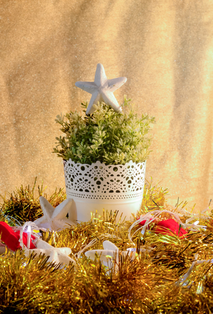 small tree: retro look Christmas decorations with ,bell,small tree on white pot, and artificial flower Stock Photo