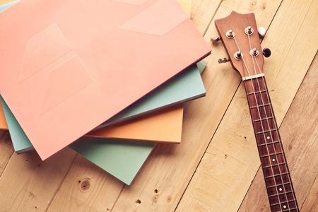ukulele with books on the texture wood floor with vintage color concept