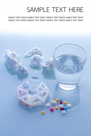 Pills planner with weekly medication capsules in it, glass of water  with copy space above