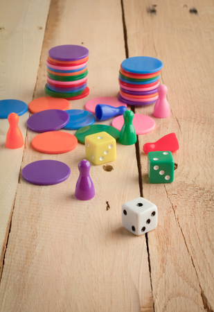 colorful dice and chips on wooden table background