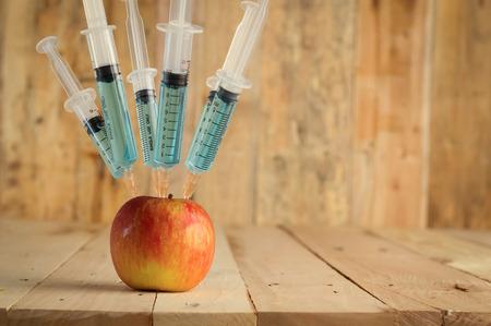 inyeccion: La inyecci�n en manzana roja - concepto de la fruta modificada gen�ticamente y una jeringa con alimentos GMO colorido qu�mica Foto de archivo