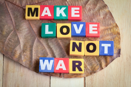 counterculture: Wooden Blocks with the text make love not war on wooden background