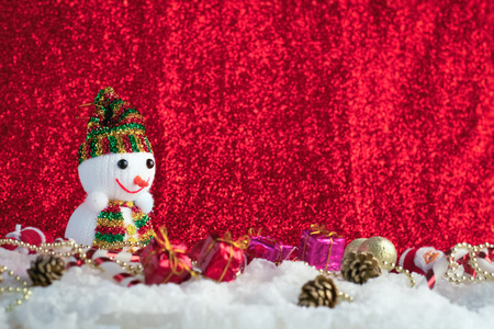 Santa Claus and Christmas balls on snow wuth red shiny background Stock Photo
