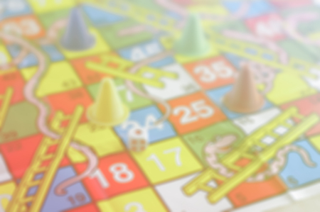 horseplay: blur colorful play figures and dice on paper board .jpg Stock Photo