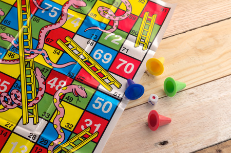 colorful play figures with dice on board and wooden table