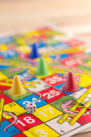 horseplay: Children game with board and dice on wooden table