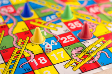 horseplay: colorful play figures with dice on board and wooden table