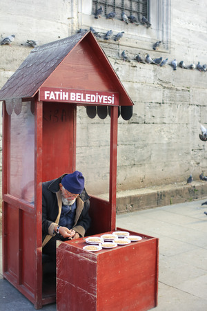 alienated: Tulkey Istunbul december 2014 old man in red station selling food for birds Editorial