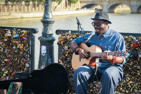 affixed: Paris France October 21 2013 : Unidentified musician plays guitar and singing on the Love Locks bridge