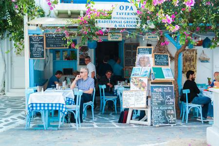 myconos: Myconos, Greece - November 21, 2013 : tourists at restaurant on the beach near the four famous windmills of Mykonos, Greece