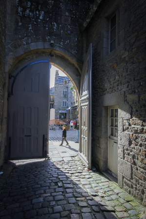st  malo: St Malo France November 15 2513 :Narrow cobblestone street with old buildings viewed though stone arch in medieval town St Milo France