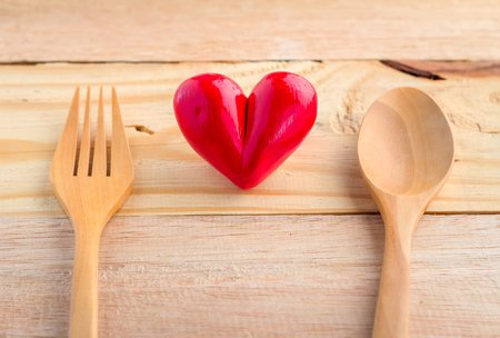 detrimental: heart with wooden spoon and fork on wooden background: health concept