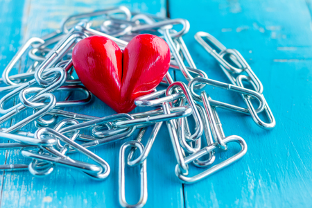 forbidden love: heart tied with chains on blue color backgrpund Stock Photo