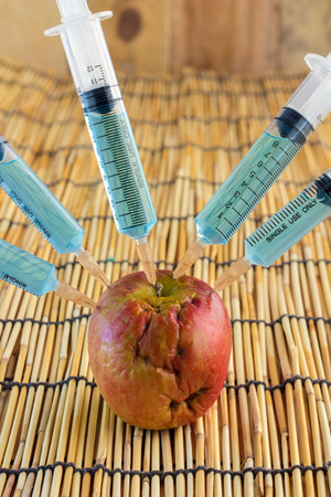 apple gmo: Injection into red apple - Concept for Genetically modified fruit and syringe with colorful chemical GMO food on bamboo mat background
