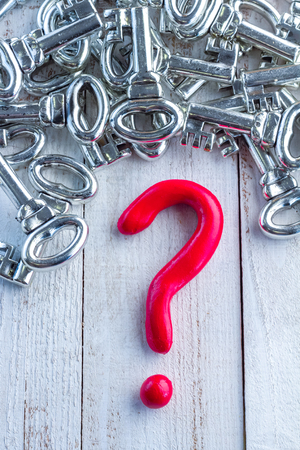 solver: red question mark and silver keys on wooden table business solution concept.jpg