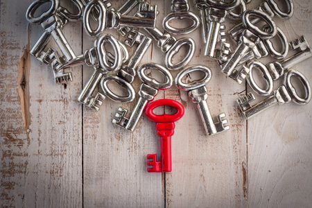 right red vintage key with silver keys on wooden floor success concept