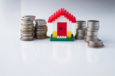economic rent: Mortgage concept by money house from the coins on white background