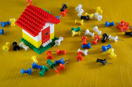 yellow tacks: house model with set of color pins on yellow leather floor
