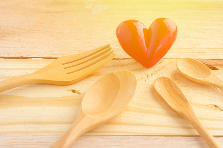 detrimental: heart with wooden spoon and fork on wooden background Stock Photo