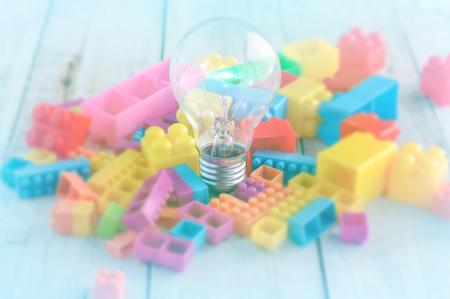 economia: Bombilla del concepto creativo y juguetes de bloques de colores en blanco suelo de madera
