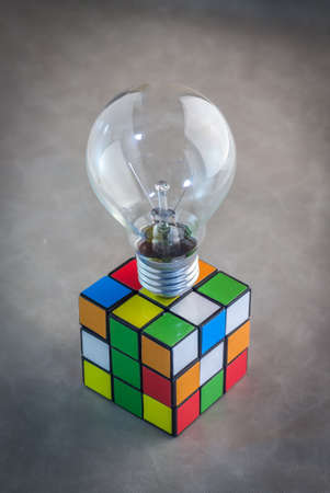 rubik: thailand febuary 10 2015 Rubiks Cube and bulb on grey background Rubiks cube invented by a Hungarian architect Erno Rubik in 1974.