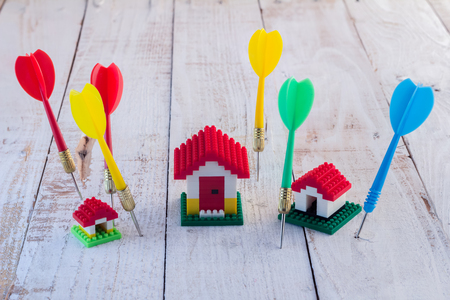 mortage: Business concept with mini model house and darts on wooden background Stock Photo
