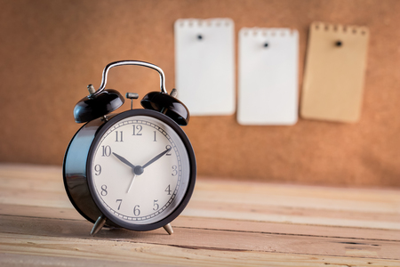 note paper pin: alarm clock with note paper pin on cork board background  on wooden floor Stock Photo