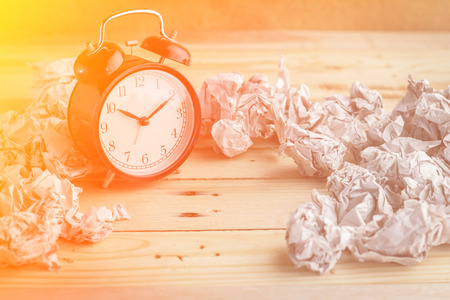 waste paper: Clock with waste paper  on wooden background